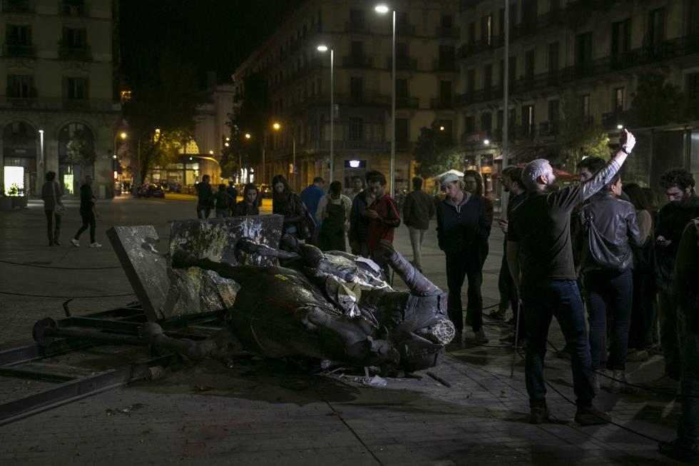 Um grupo de pessoas contempla a estátua de Franco derrubada.