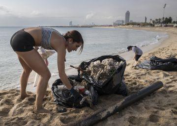 Una trabajadora de la hostelería recogiendo basura en la Mar Bella