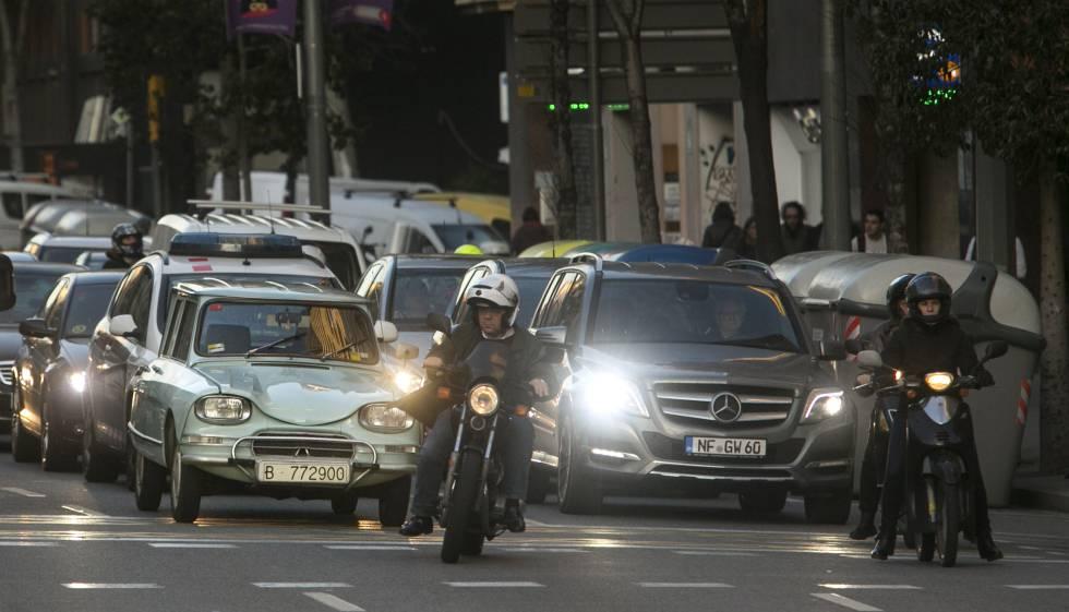 Varios vehículos esperan en un semáforo de la caller de Aragó, en Barcelona.