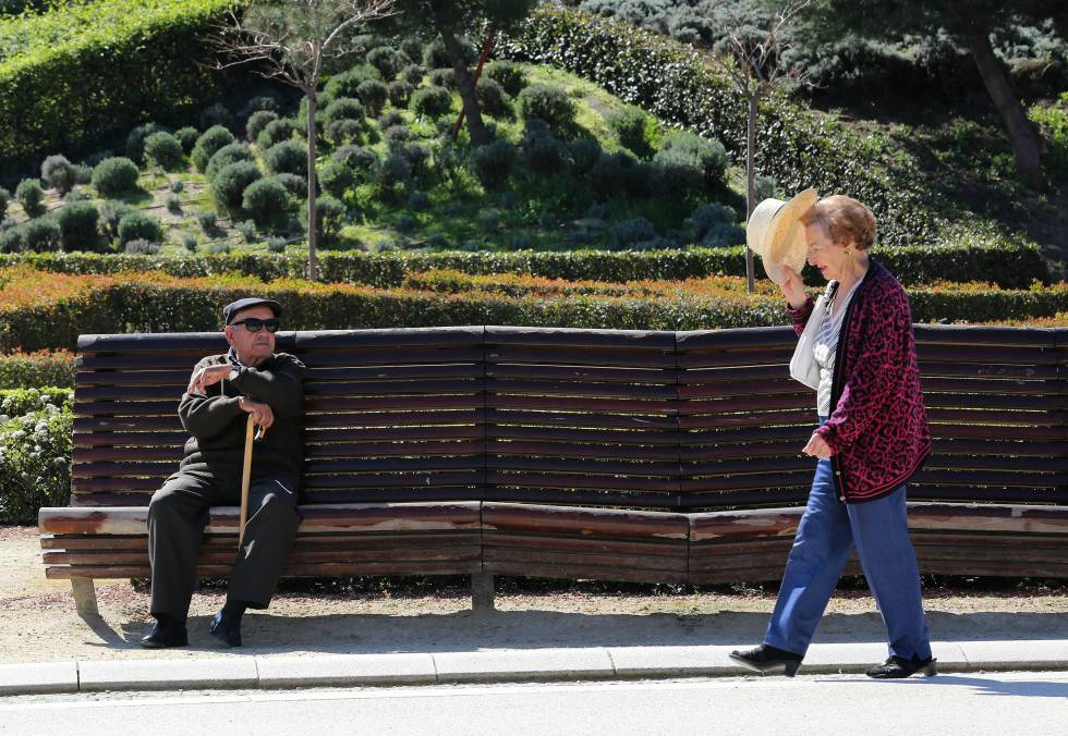 Dos jubilados toman el sol en la zona de Madrid Río.