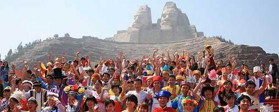 Decenas de chinos ataviados con trajes tçipicos regionales, durante la inauguración de la estatua.