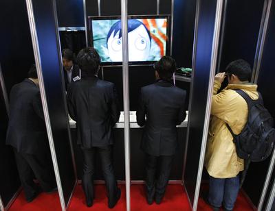 Asistentes a la Feria Del Anime de Tokio ven con unas gafas especiales una animación en 3D en televisores.