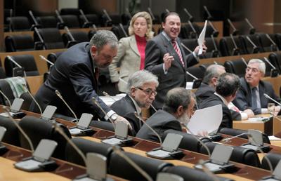 Los diputados Pedro Azpiazu (PNV, de pie), Josep Sánchez Llibre (CiU) y Francisco Fernández Marugán (PSOE) conversan en la Comisión de Economía del Congreso, donde se debate la 'ley Sinde', mientras el diputado del PP, Vicente Martinez Pujalte, en el fondo de la imagen gesticula