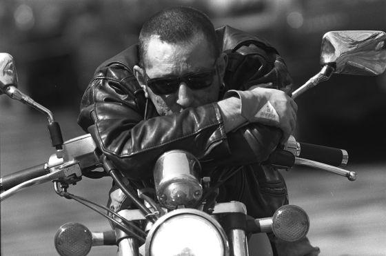 Enrique Sierra cantante de Radio Futura sentado en una moto