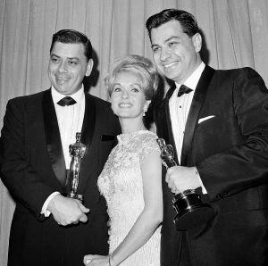 Robert Sherman (a la izquierda) y su hermano Richard reciben en 1965, de manos de Debbie Reynolds, sus oscars por Mary Poppins.