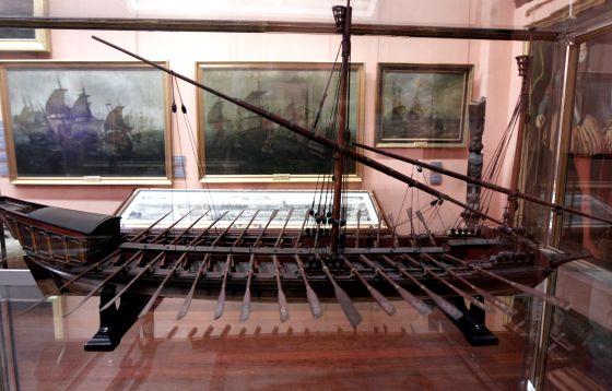 Modelo de galera menor o galeota en el Museo Naval y, abajo, cédula real de 1642 que libera a un galeote.