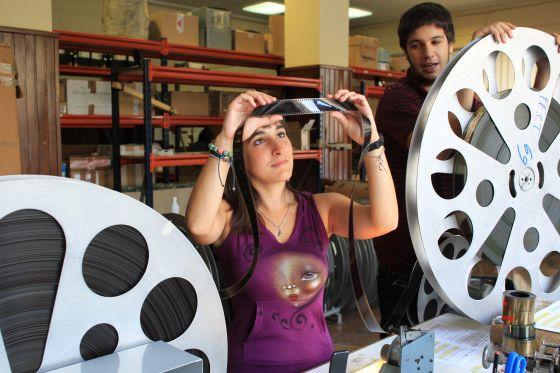 Dos miembros del equipo técnico de Zinemaldia revisan una película.