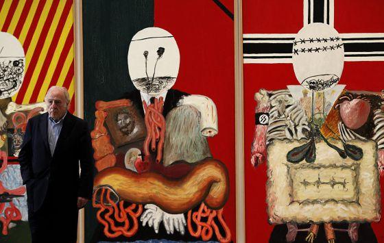 El pintor Eduardo Arroyo posa junto a su obra 'Los cuatro dictadores', que forma parte de la nueva sección de la colección permanente del Museo Reina Sofía, presentada hoy, lunes 21 de mayo, bajo el titulo '¿La guerra ha terminado? Arte en un mundo dividido (1945-1968)', que recorre las transformaciones artísticas en la posguerra con obras de Francis Bacon, Philip Guston, Darío Villalba, Jean Tinguely, Yves Klein, Raimond Hains, Eduardo Arroyo o Val del Omar.
