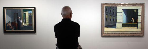 Exposición de Edward Hopper en el museo Thyssen Bornemisza de Madrid Tomás Llorens comisario de la exposición contempla las obras 'Hotel by the railroad', a la izquierda, y 'New York Office', a su derecha. / GORKA LEJARCEGI