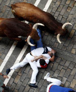 Dos toros de la ganadería salmantina de El Pilar pasan por encima de dos mozos caídos durante su carrera por el tramo de la Calle Estafeta.