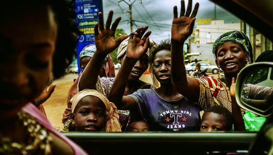 Varias personas se agolpan junto al coche de Oumou.