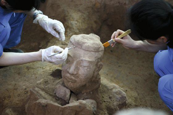 Arqueólogos chinos trabajan en la limpieza de uno de los nuevos guerreros de terracota recién descubiertos en Xian (China).