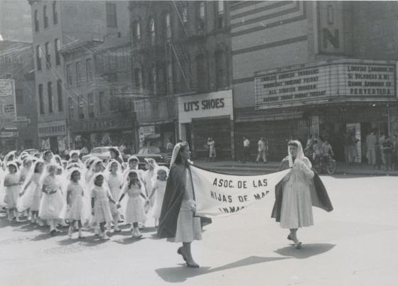 """La Asociación de las Hija de María Inmaculada. En la marquesina de los cines detrás de este desfile se puede leer: """"All Spanish Program"""" (foto exclusiva para El País, cortesía de Artur Balder)."""