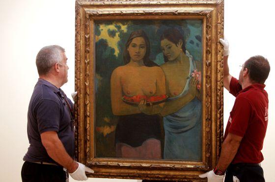 Operarios del museo colocan 'Dos mujeres tahitianas' en la exposición 'Gauguin y el exotismo'.