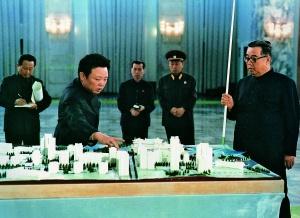 Kim Jong-il explicando el proyecto de construcción de un nuevo barrio a su padre, Kim Il-Sung, en 1980.
