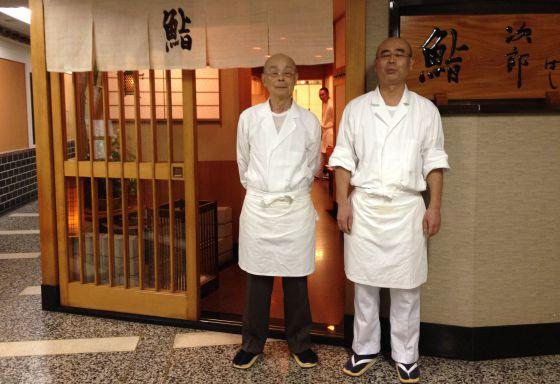 Jiro Ono (a la izquierda), junto a su hijo Yoshikauzu, en la entrada de su restaurante Sukiyabashi Jiro Honten, en una estación del metro de Tokio.