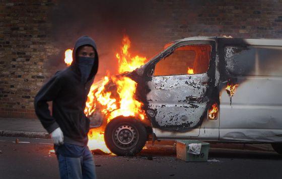 Un joven participa en los disturbios acaecidos en el verano de 2011 en Londres.