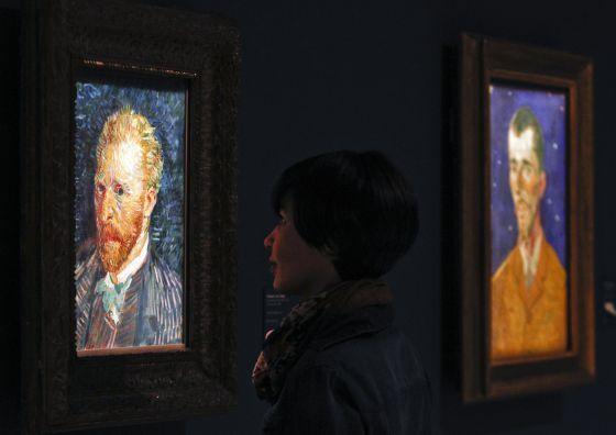 Una visitante contempla el 'Autorretrato' de 1887 de Van Gogh; a su lado, 'Retrato de Eugène Boch', obra de 1888.