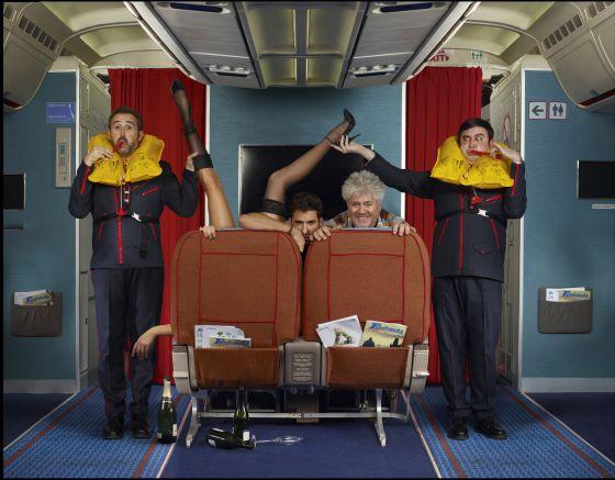 Javier Cámara y Carlos Areces, de pie, y Miguel Ángel Silvestre y Pedro Almodóvar, asomados tras los asientos en 'Los amantes pasajeros'.