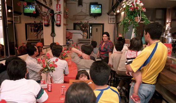 Varias personas ven un partido de fútbol en un bar.