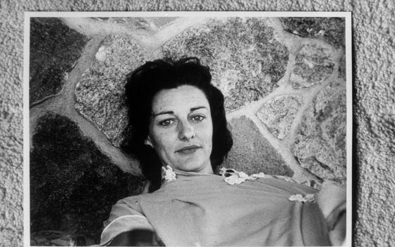 Anne Sexton tumbada en un patio de piedra.