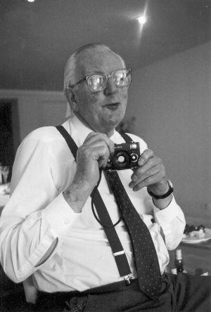 Tom Sharpe, retratado con su inseparable cámara de fotos a mediados de los noventa.