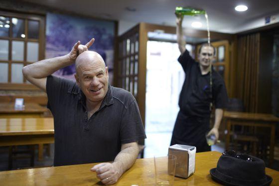 David Simon aguarda a ser servido una sidra recién escanciada en Casa Alvarín, en Avilés.