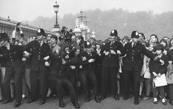 La policía trata de contener a los fans de The Beatles a las puertas de Buckingham Palace, donde fueron condecorados con la medalla del Imperio británico en octubre de 1965.