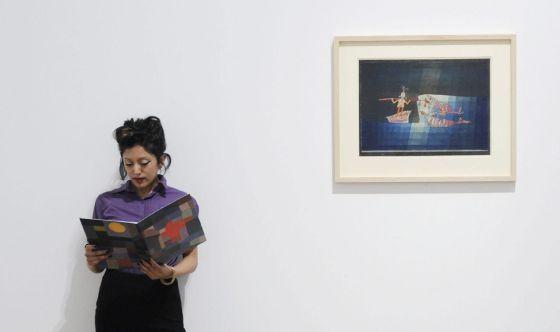 Una mujer posa junto a la obra