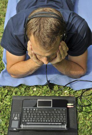 Un hombre escucha música en su ordenador.