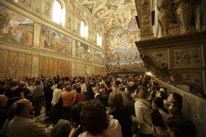 Una multiutud de turistas contemplan los frescos de Miguel Ángel.