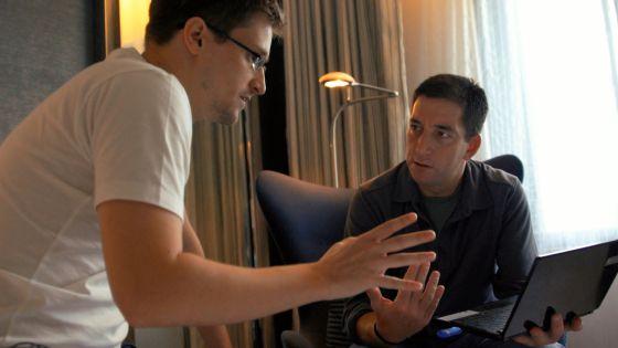 Snowden y Greenwald hablando en su habitación en Hong Kong, en una escena del documental.