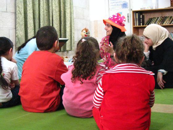 Rana Dajani, con sombrero, lee un cuento a varios niños en Amán.