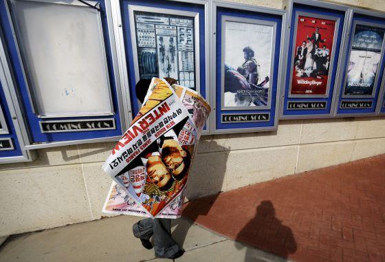 Un empleado retira los carteles de 'La entrevista' de un cine de Atlanta.