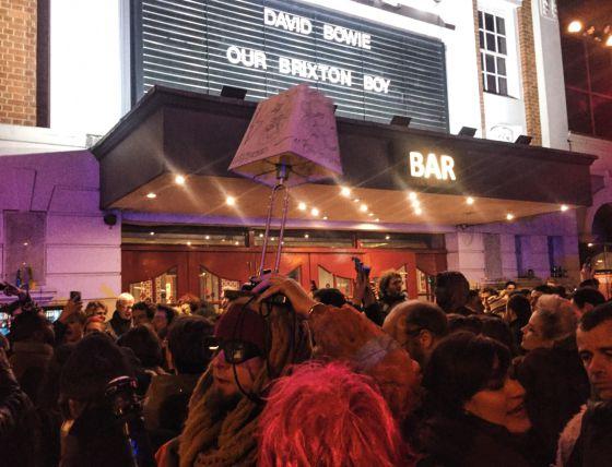 Fans ante el cine Ritzy, que homenajea en su cartel a Bowie.