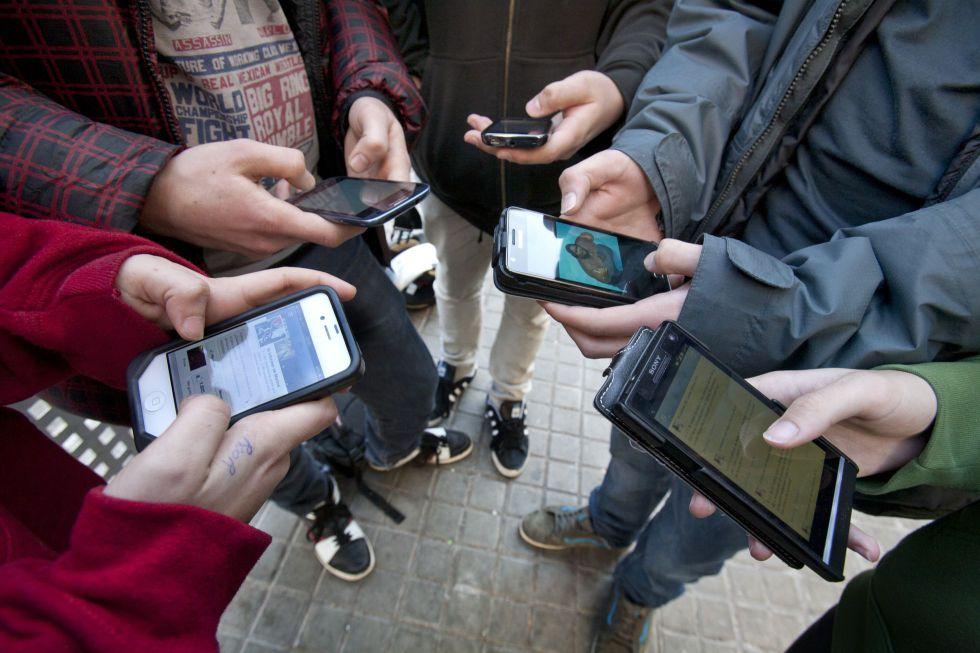 Jóvenes de un instituto barcelonés consultan las redes sociales a través del móvil.