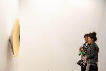 Dos visitantes de Zona Maco frente a una de las obras.