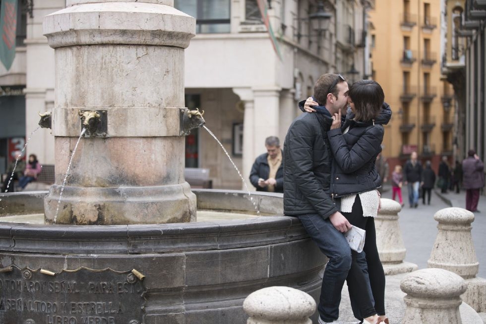 Una pareja de turistas se besa en la fuente del torico en Teruel, hoy, día de San Valentín.