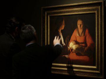 Visitantes contemplan la obra 'El recién nacido' de De La Tour, en el Prado.