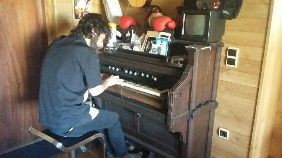 Quique González toca su armonio en su casa.