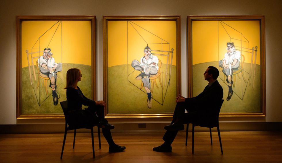 Visitors admire Francis Bacon's 'Three Studies of Lucian Freud' at Christie's in London.