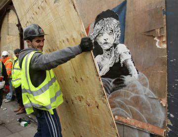 Un hombre cubre hoy con un tablón de madera el grafiti de Banksy ante la Embajada de Francia en Londres.