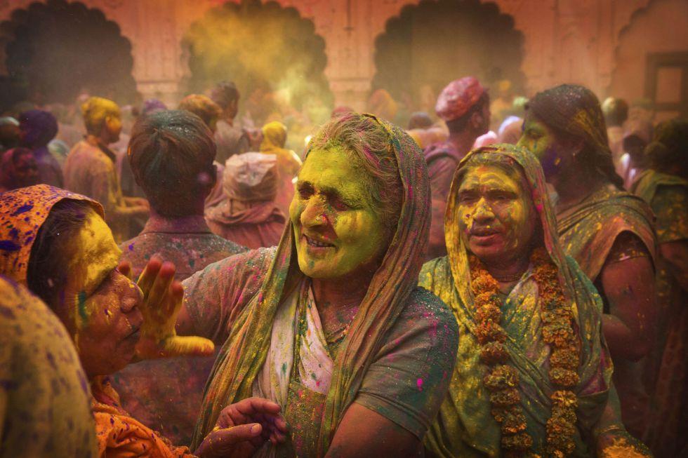 Viudas hindús se pintan la cara con polvos de colores en el templo Gopinath.