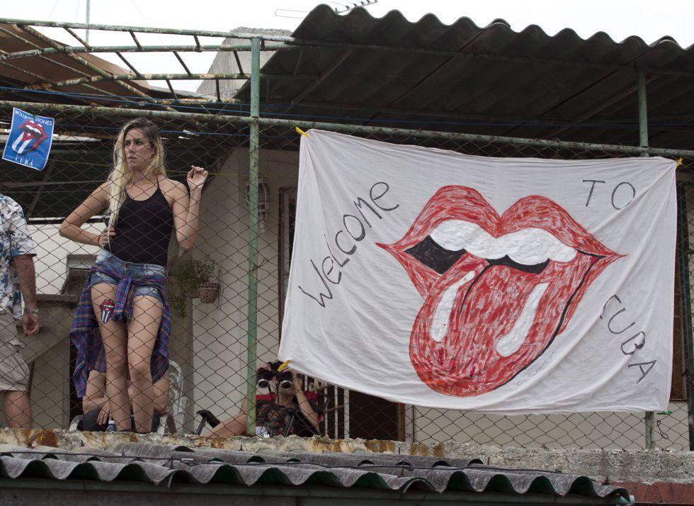 Una cubana mira a los Rolling Stones desde una azotea en La Habana.