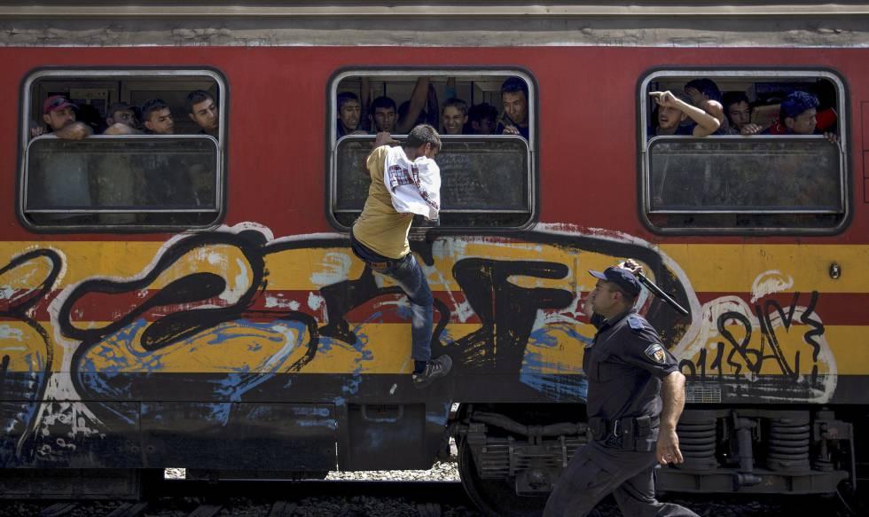 Una de las fotografías premiadas. Un policía trata de impedir a un refugiado que se suba a un tren en Macedonia