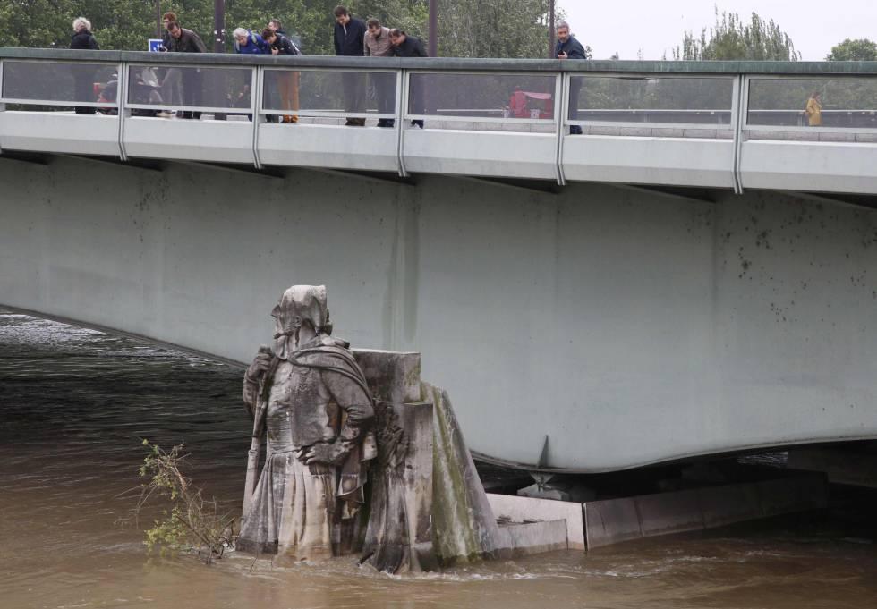 Parisienses observando una estatua del Pont de l'Alma, cubierta por el agua del Sena.