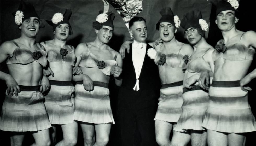 Hombre en esmoquin rodeado de seis travestis. Alemania, invierno de 1937.
