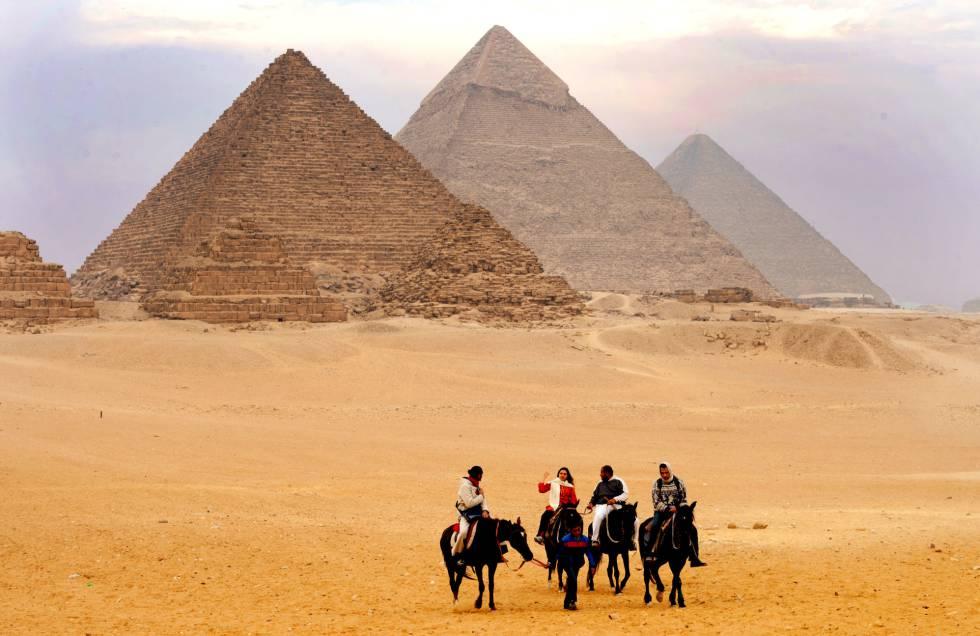 Turistas frente a las tres pirámides de Guiza.