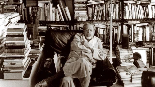 El escritor Guillermo Cabrera Infante, rodeado de libros en su casa de Londres, en 1998.