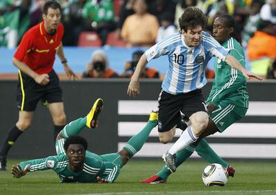 Messi se lleva el balón entre Haruna (a la izquierda) y Odiah.